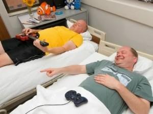 Dois senhores em camas separadas jogando videogame e tocando guitarra