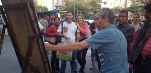 Pessoas assistem a professor dando aula na rua