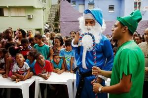 Crianças observam Papai Noel de azul e gnomo alto