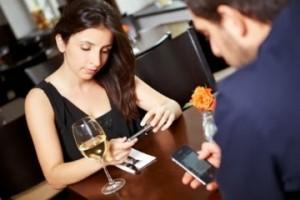 Casal com celular no restaurante