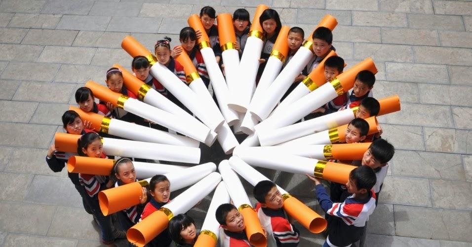 Crianças chinesas seguram cigarros gigantes