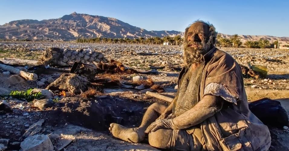 Amoo Hadji sentado no chão com montanhas ao fundo