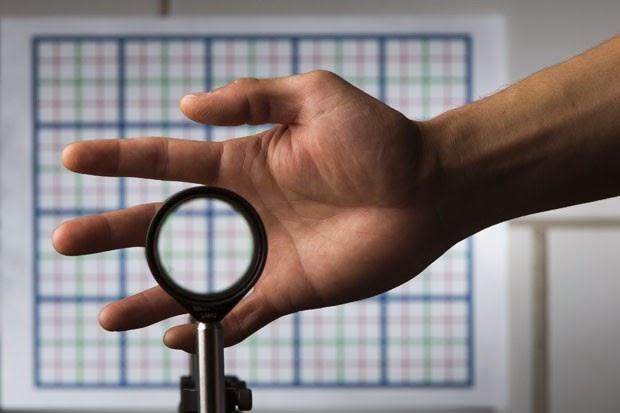 Mão atrás da lente de invisibilidade