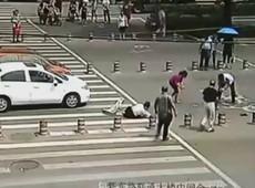 Pedestres ajudam chinesa atropelada a recuperar o dinheiro espalhado na rua
