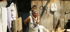 Pai adotivo carrega o filho doente nas costas por favela para levá-lo à escola