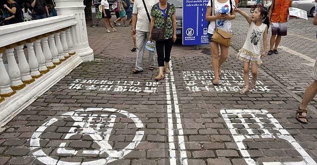 Cidade chinesa cria faixa exclusiva na calçada para pedestres com celular